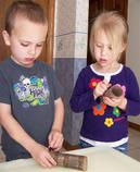 Two kids making a craft project with paper tubes.
